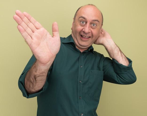 Opgewonden man van middelbare leeftijd die groene t-shirtpunten draagt met de hand aan de zijkant die de hand achter het hoofd zet dat op olijfgroene muur wordt geïsoleerd