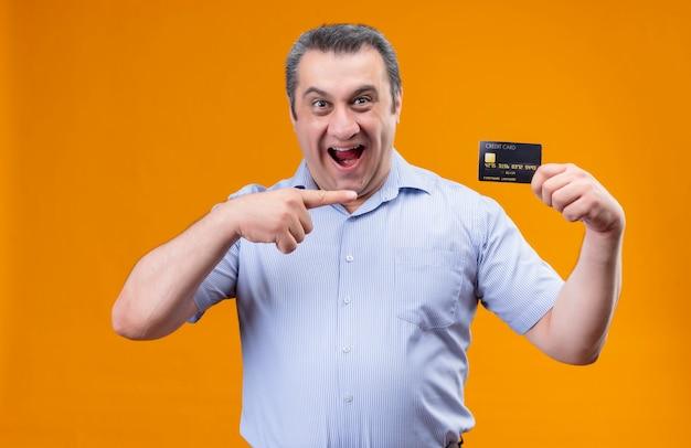 Opgewonden man van middelbare leeftijd met blauwe verticale gestripte shirtpunten met een creditcard van de wijsvinger die de mond open houdt