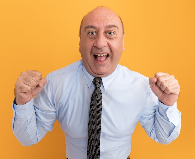Opgewonden man van middelbare leeftijd met een wit t-shirt met stropdas met ja gebaar geïsoleerd op een oranje muur orange