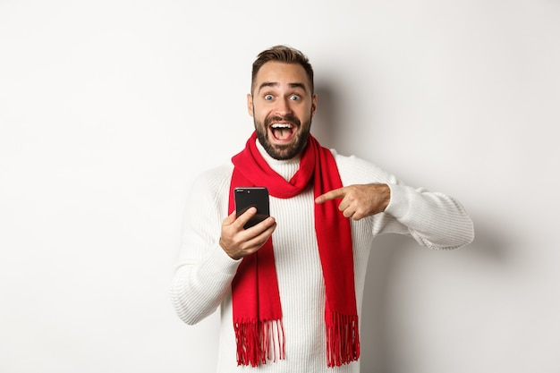 Opgewonden man vertelt over aanbieding op mobiele telefoon, wijst naar smartphone en kijkt verbaasd, staande tegen een witte achtergrond.