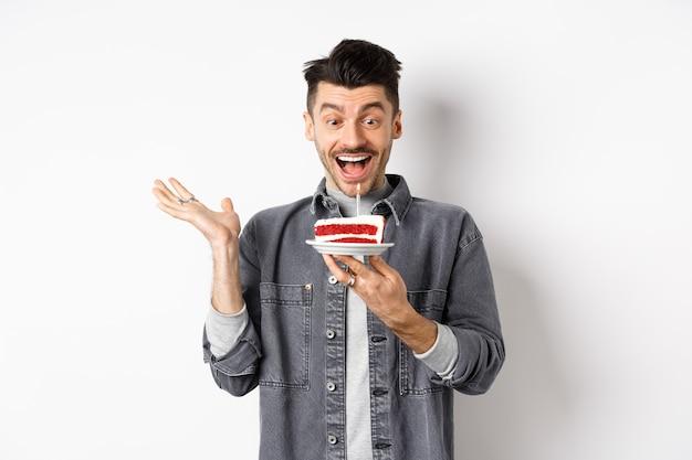 Opgewonden man viert verjaardag, gelukkig kijken naar bday cake met kaars, wens maken, permanent blij tegen witte achtergrond.