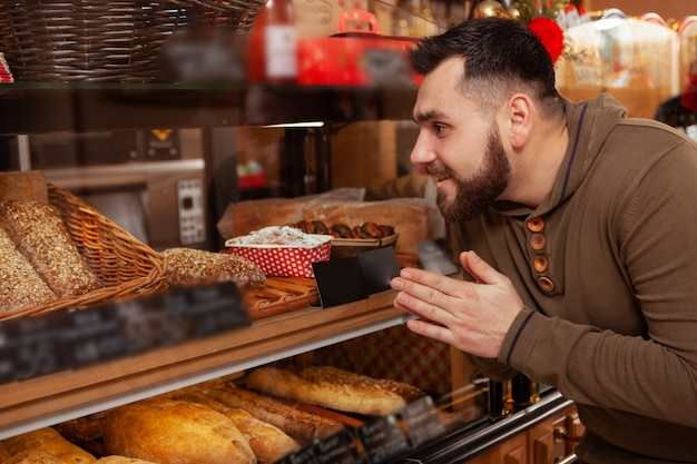 Opgewonden man winkelen voor gebak bij plaatselijke bakker, kijkend naar de vitrine
