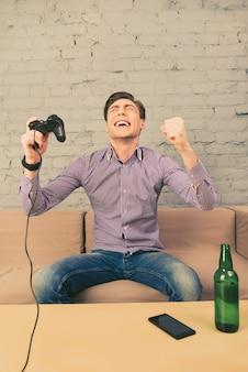 Opgewonden man winnen van videogame en zegevieren met opgeheven handen