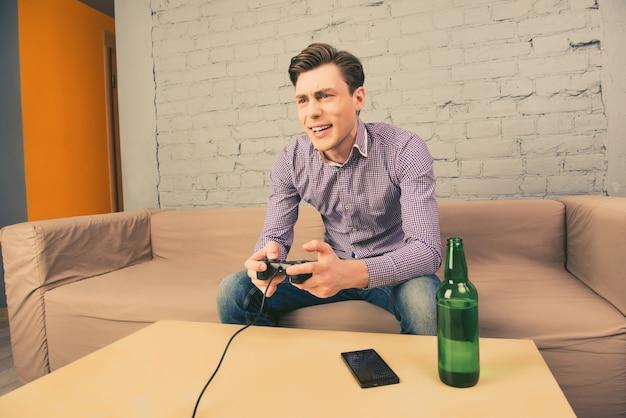 Opgewonden man zittend op de bank met flesje bier en spelen van videogames