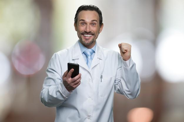 Opgewonden mannelijke arts die smartphone vasthoudt en zich verheugt. medische jas dragen. samenvatting onscherpe achtergrond.