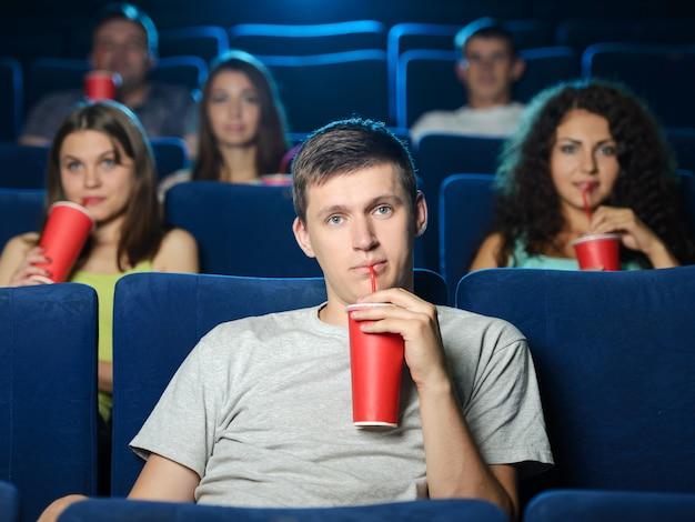Opgewonden mannen kijken naar film in de bioscoop en drinken frisdrank
