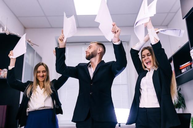 Opgewonden medewerkers dansen op kantoor, personeelsfeest, positief team tevreden met resultaat
