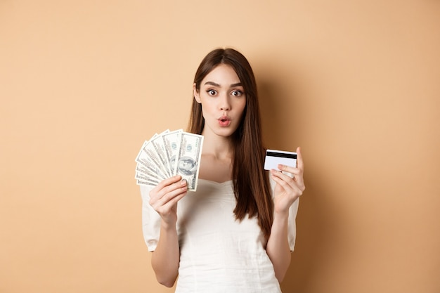 Opgewonden meisje dat dollarbiljetten en plastic creditcard toont, wauw zegt met verbaasd gezicht, staande op beige.