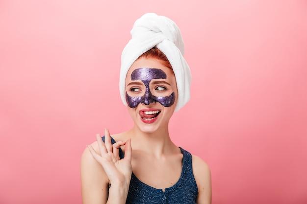 Opgewonden meisje dat goed teken toont tijdens kuur. studio shot van gelukkige jonge vrouw met handdoek en gezichtsmasker geïsoleerd op roze achtergrond.
