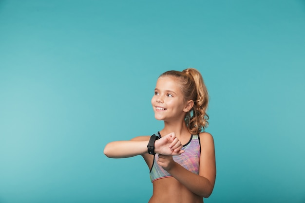 Opgewonden meisje dat sportkleding draagt die slim horloge gebruikt dat over blauwe muur wordt geïsoleerd