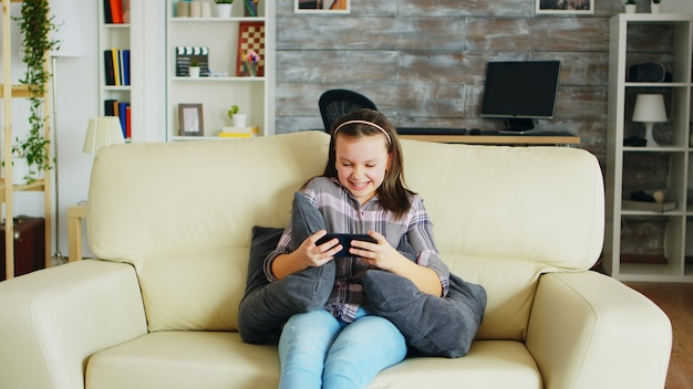 Opgewonden meisje dat videogames speelt op haar telefoon, zittend op de bank.