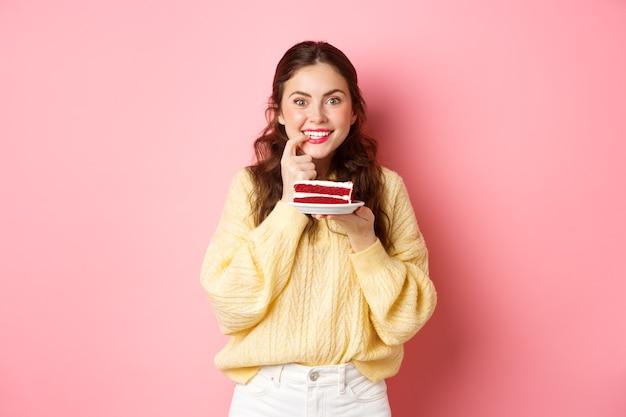 Opgewonden meisje denkt aan het eten van heerlijke cake, vinger bijt van verleiding en nadenkend naar de camera kijken, denk aan calorieën in het dessert, roze muur.