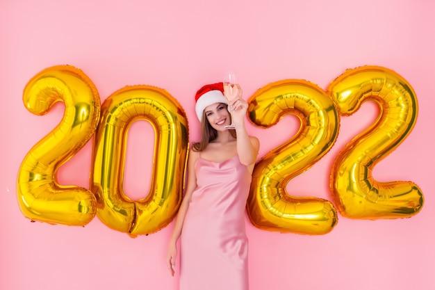Opgewonden meisje heft glas champagne op in kerstmuts gouden luchtballonnen nieuwjaarsconcept