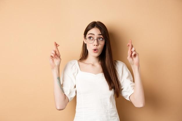 Opgewonden meisje hoopt droom die uitkomt, wens te maken met gekruiste vingers, opzij kijken en bidden, staande op beige achtergrond.