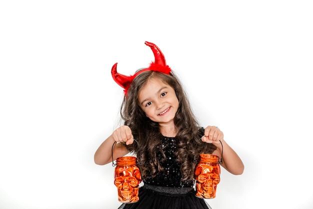 Opgewonden meisje in een heksenkostuum met schedellantaarns op een witte studioachtergrond copyspace