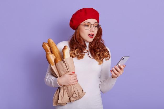 Opgewonden meisje in rode baret en witte trui poseren geïsoleerd op lila ruimte