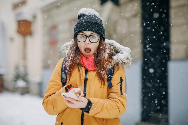 Opgewonden meisje met een positief mobiel telefoongesprek in de straat