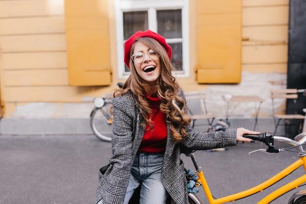 Opgewonden meisje met krullend kapsel positieve emoties uitdrukken in warme dag, lachen naar camera