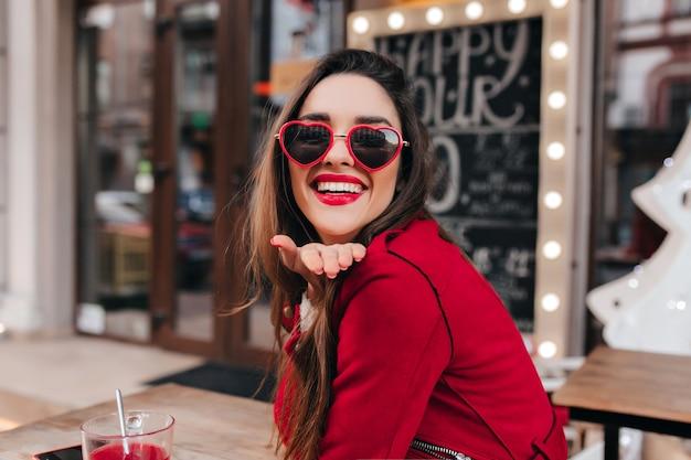 Opgewonden meisje met lichtbruin haar luchtkus verzenden in café