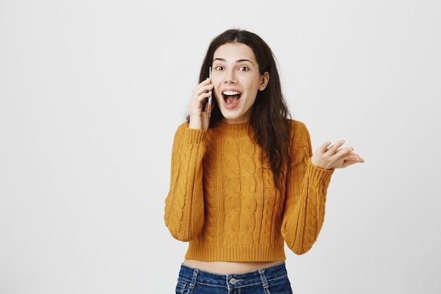 Opgewonden meisje ontvangt geweldig nieuws via telefoongesprek, praten op smartphone