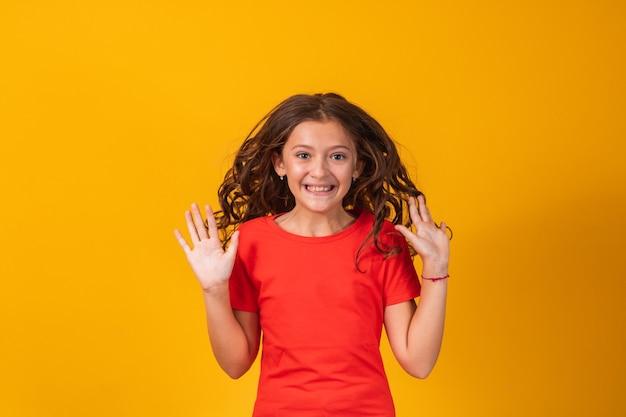 Opgewonden meisje springen op gele achtergrond. expressief meisje geschokt op gele achtergrond.