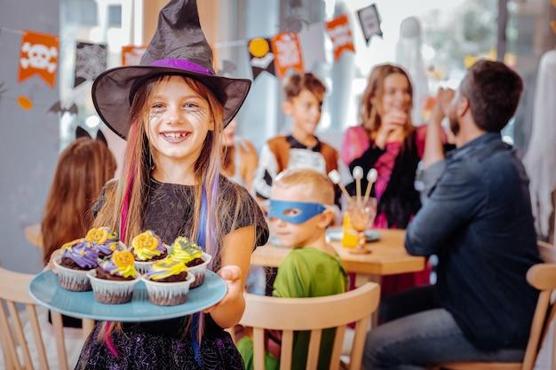 Opgewonden meisje. stralend gelukkig meisje dat halloween-kostuum draagt dat zich opgewonden voelt bedrijf plaat met heldere cupcakes