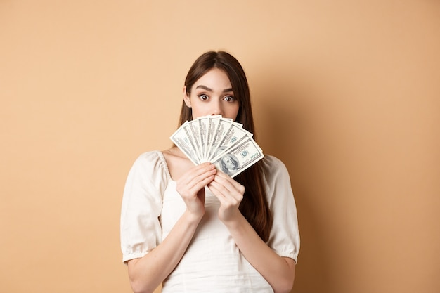 Opgewonden meisje tonen dollarbiljetten en wenkbrauwen verhogen verbaasd, geld verdienen, staande op beige achtergrond.