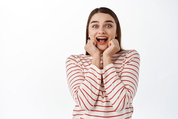 Opgewonden meisje vol ontzag, schreeuwt van vreugde en verbazing, houdt handen bij mond, starend naar iets geweldigs, zie superster en kijk verbaasd, staande over witte muur