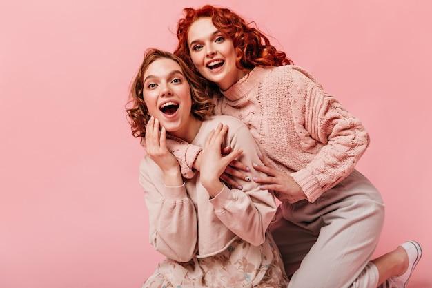 Opgewonden meisjes omhelzen elkaar met een oprechte glimlach. vooraanzicht van gelukkige vrienden die op roze achtergrond lachen.