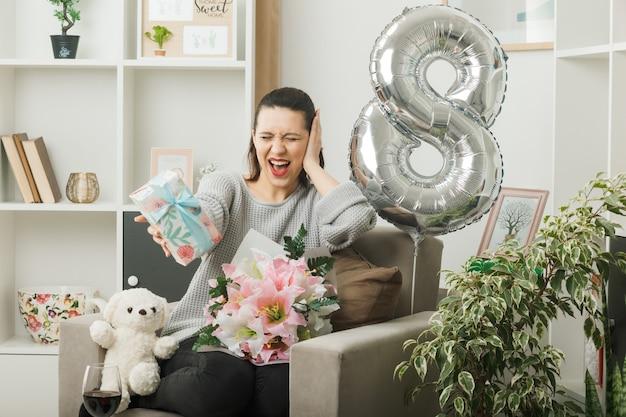 Opgewonden met gesloten ogen hand op wang leggen mooi meisje op gelukkige vrouwendag met cadeau, zittend op een fauteuil in de woonkamer