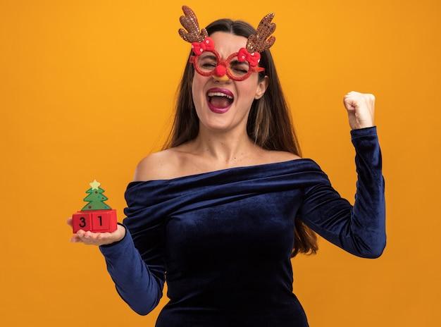 Opgewonden met gesloten ogen jong mooi meisje draagt blauwe jurk en kerst bril houden speelgoed weergegeven: ja gebaar geïsoleerd op een oranje achtergrond