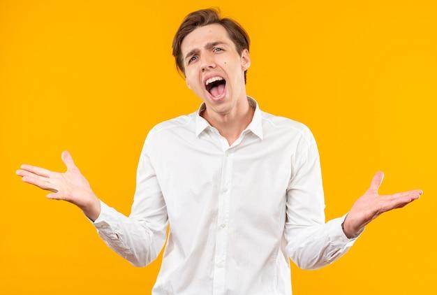 Opgewonden met gesloten ogen jonge knappe kerel met een wit overhemd dat handen uitspreidt die op een oranje muur zijn geïsoleerd