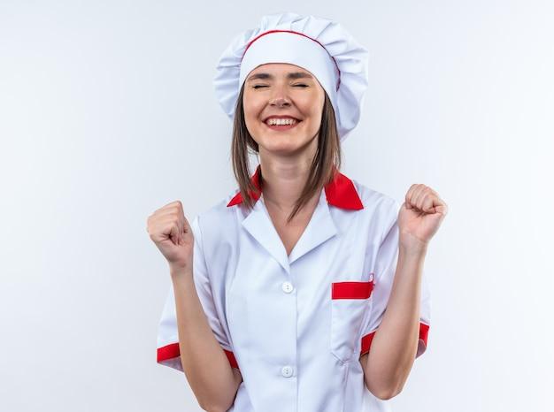 Opgewonden met gesloten ogen jonge vrouwelijke kok in uniform van de chef-kok met ja gebaar geïsoleerd op een witte muur