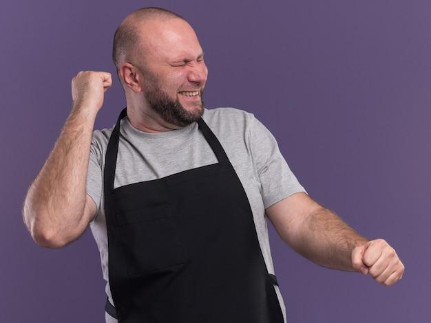 Opgewonden met gesloten ogen slavische mannelijke kapper van middelbare leeftijd in uniform met ja gebaar geïsoleerd op paarse muur