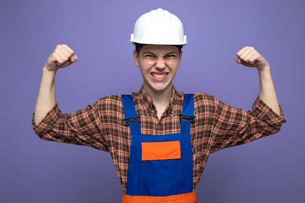 Opgewonden met ja-gebaar jonge mannelijke bouwer die uniform draagt