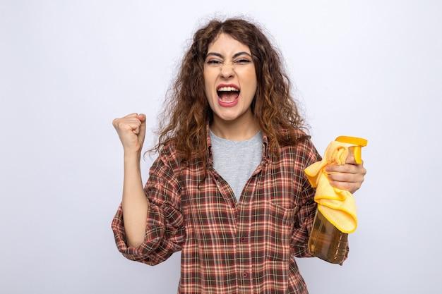 Opgewonden met ja gebaar jonge schoonmaakster met reinigingsmiddel met vod geïsoleerd op een witte muur