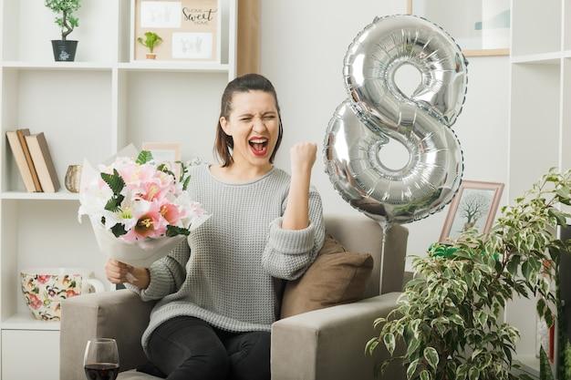 Opgewonden met ja gebaar mooi meisje op gelukkige vrouwendag met boeket zittend op fauteuil in woonkamer