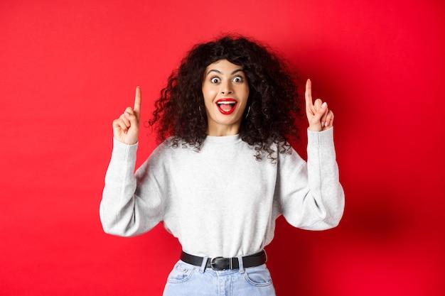 Opgewonden modern meisje dat promo toont die met de vingers omhoog wijst en verbaasd glimlacht en groot nieuws vertelt dat o...