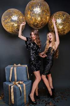 Opgewonden modieuze jonge vrouwen in luxe zwarte jurken nieuwjaarsfeest vieren met grote ballonnen met gouden tinsels. plezier hebben, cadeautjes, positiviteit uiten.