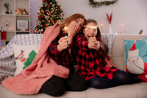 Opgewonden moeder en dochter houden wonderkaarsen bedekt met deken zittend op de bank en genieten van kersttijd thuis