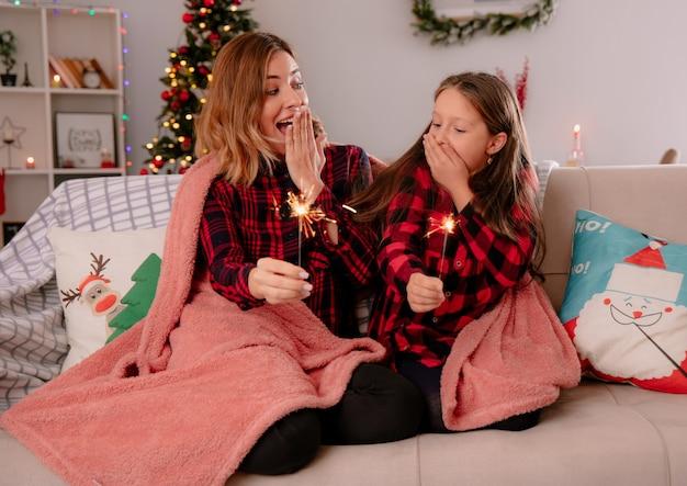 Opgewonden moeder en dochter leggen hand op mond en houden wonderkaarsen bedekt met deken zittend op de bank en genieten van kersttijd thuis
