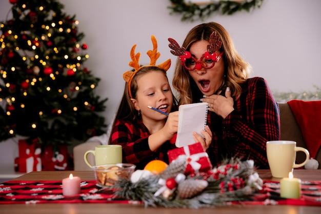Opgewonden moeder in rendierglazen laptop kijken met dochter zittend aan tafel genieten van de kersttijd thuis