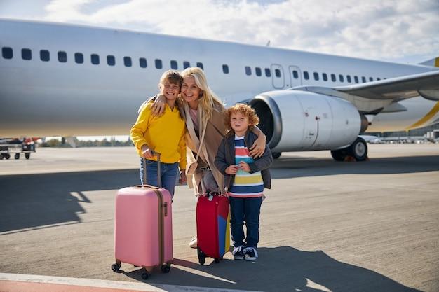 Opgewonden moeder met kinderen die bij een vliegtuig staan