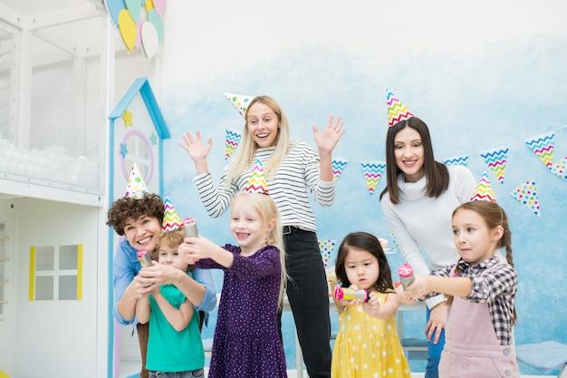 Opgewonden moeders plezier met kinderen op verjaardagsfeestje