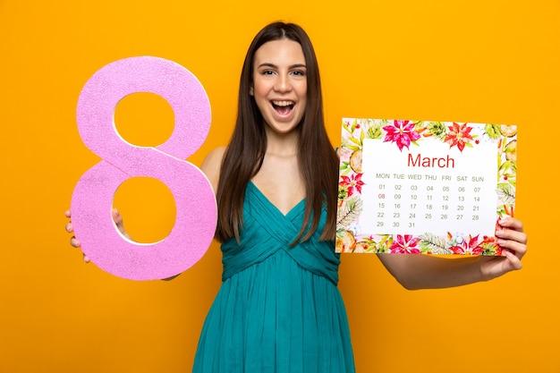 Opgewonden mooi jong meisje op gelukkige vrouwendag met kalender met nummer acht