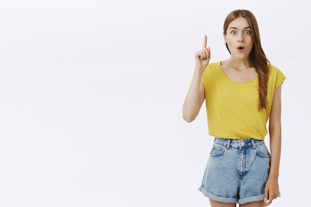 Opgewonden mooi meisje dat idee suggereert, vinger opsteken, denkplan