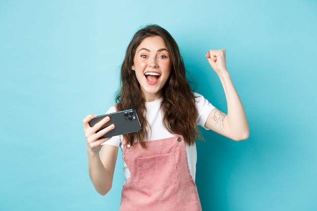 Opgewonden mooi meisje dat op mobiele telefoon wint, smartphone vasthoudt en ja schreeuwt met een vrolijk gezicht en vuistpomp, verbaasd glimlachend naar de camera, blauwe achtergrond