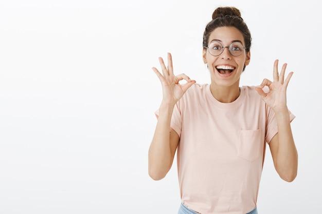Opgewonden mooi meisje met bril poseren tegen de witte muur