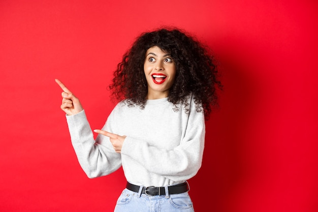 Opgewonden mooi meisje met krullend haar en rode lippen, kijkend en wijzende vingers naar links met verbaasd gezicht, banner tonen, staande op studio achtergrond.