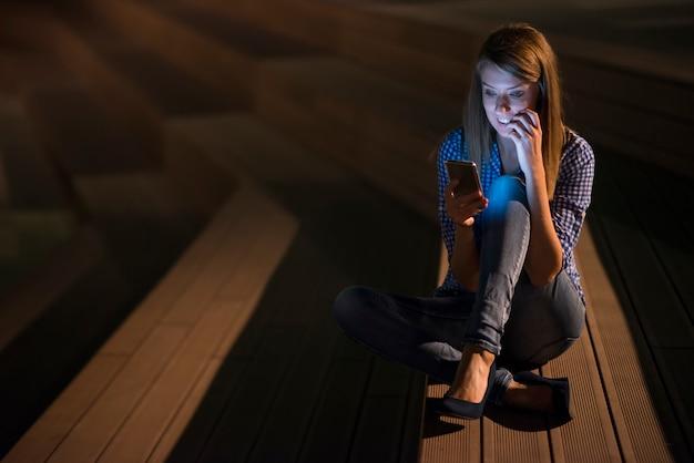 Opgewonden mooi meisje ontvangen een sms bericht met goed nieuws in een mobiele telefoon buiten